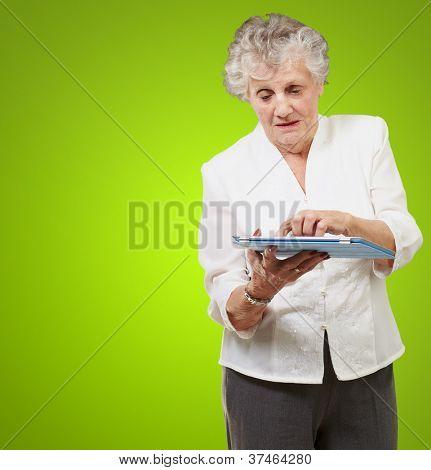 Senior woman using ipad isolated on green background