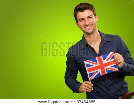 A Young Man Holding A Flag Of United Kingdom On Green Background