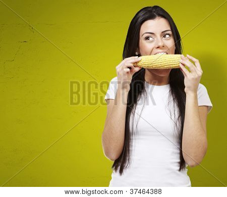 woman eating a delicious corncob against a yellow background