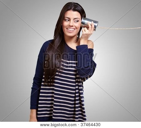Female Holding A Metal Tin As A Telephone On A gray Background