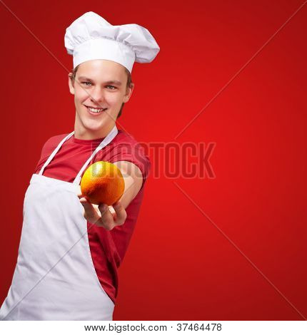 portrait of young cook man offering orange over red background