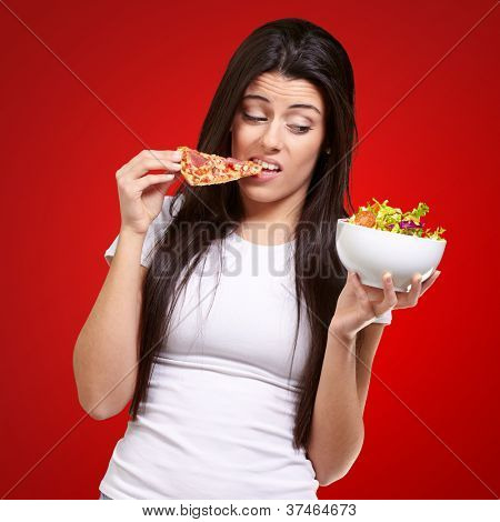 portrait of young woman eating pizza and looking salad over red