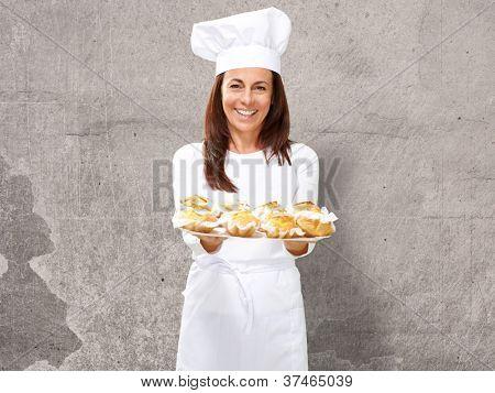 Chef mujer sosteniendo alimentos horneados, interior