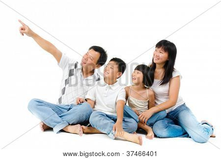 Happy Asian family sitting on floor and pointing over white background