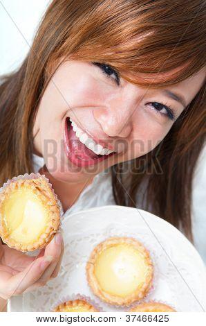 Close up young Asian woman enjoying egg tart