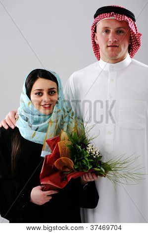 Arabic couple, wife and husband holding boquet of flowers