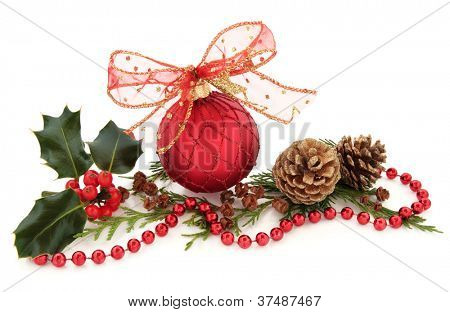 Christmas red sparkling bauble with glitter bow surrounded by holly and cedar leaf sprigs with gold pine cones over white background.