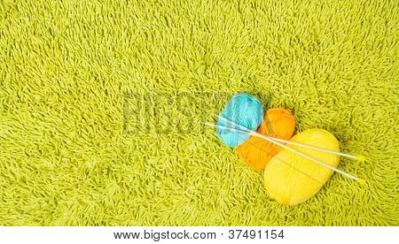 Knitting Yarn Balls And Needles Over Green Carpet Background