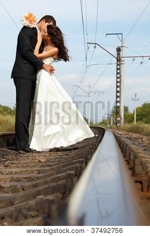 beautiful young couple bride with groom in love on railway, summertime