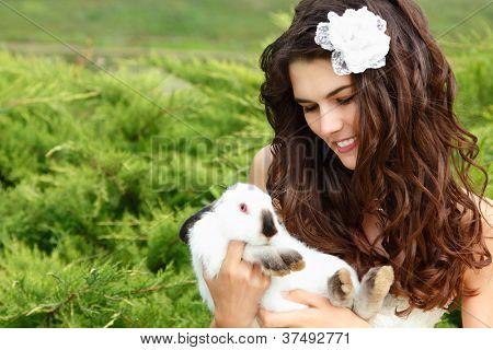 Novia joven sonriendo y sosteniendo dos conejos lindos sobre Parque naturaleza de verano al aire libre, Alicia en el ganado