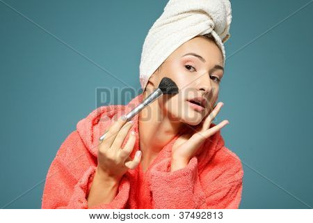 young woman putting rouge in the morning over blue background