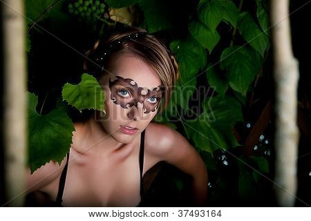 Young Girl In Fancy Carnival Mask Among Trunks Of Trees