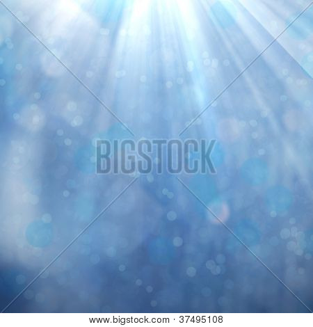 Sparkling sun beams from above on blue luminous abstract background with blurred spots of light.