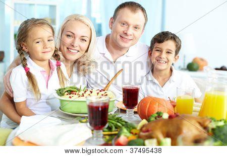 Retrato de familia feliz sentado en la mesa festiva y mirando a cámara