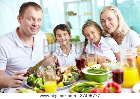 Portrait of happy family sitting at festive table and looking at camera