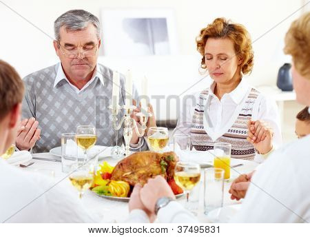 Portrait of big family sitting at festive table and praying before dinner