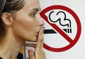 stock photo of smoking  - Lady smoking a non smoking panel background - JPG