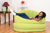image of cornrow  - happy South African child relaxing in green chair - JPG