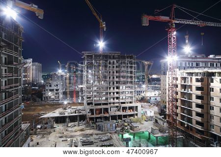 Lightening multi-storey buildings under construction and cranes at night.
