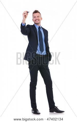 full length picture of a young business man writing something on an imaginary screen while holding his other hand in his pocket and smiling. on white background