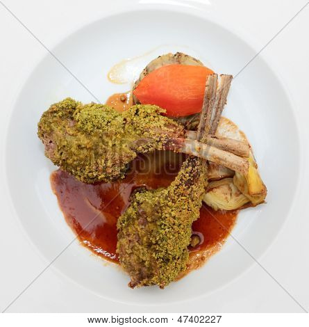 Grilled rack of lamb with pistachio in plate, isolated on black background