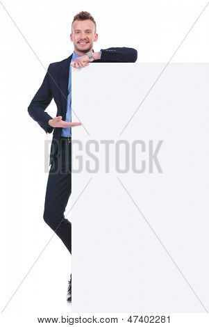 full length picture of a young business man presenting a blank pannel while smiling for the camera. on white background