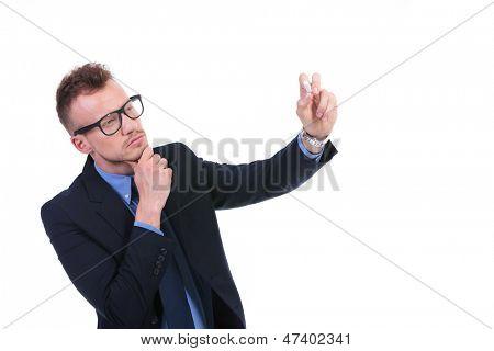 young business man writing something with chalk on an imaginary board while looking at it pensively with his hand on his chin. on white background