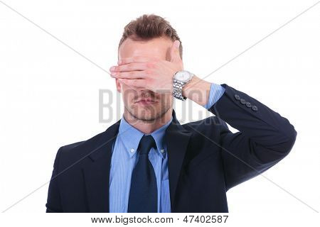 young business man covering his eyes with his hand. see no evil. on white background