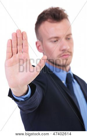 young business man showing his palm while looking away from the camera. on white background
