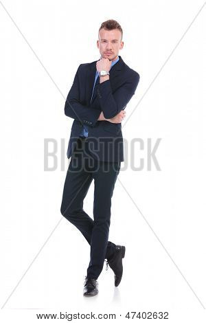 full length picture of a young business man standing in a pensive position, with his hand at his chin while looking at the camera. on white background