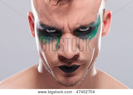 closeup of a casual young man with dramatic makeup frowning angrily. on gray background