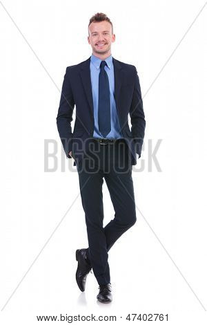 full length picture of a young business man standing with legs crossed and both hands in his pockets while smiling at the camera. on white background