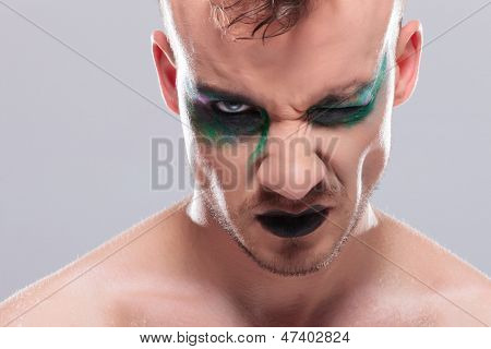 closeup of a casual young man with dramatic makeup looking at the camera with one eye. on gray background