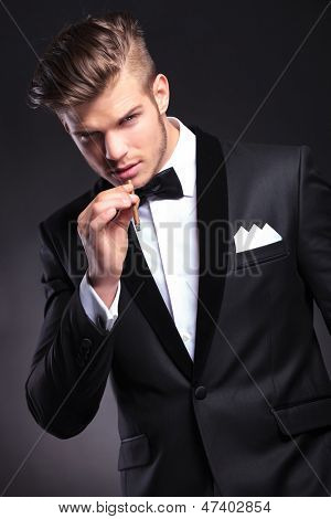 elegant young fashion man in tuxedo preparing to take a smoke from his cigarette while looking at the camera. on black background