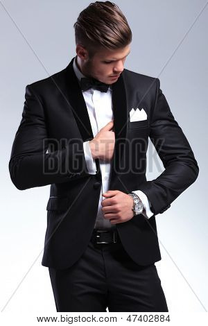 elegant young fashion man in tuxedo adjusting his suit while looking at it. on gray background