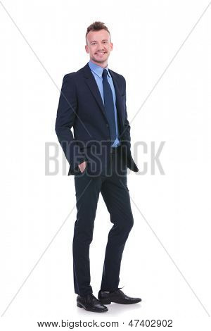 full length picture of a young business man standing with his both hands in his pockets while smiling for the camera. on white background