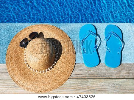 Blue slippers and hat by a swimming pool