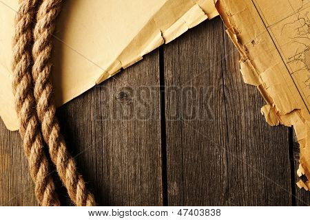 Old torn paper, map and rope on wood planks background