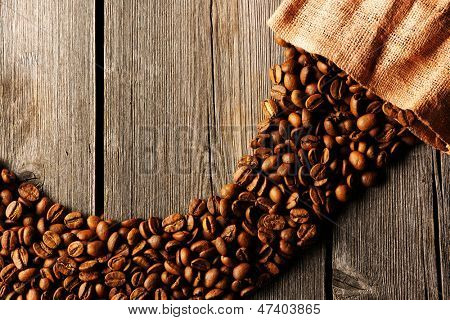 Coffee beans and bag over wooden background