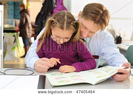 Happy girl and her father look at floor plan booklet in office. They choose apartment.
