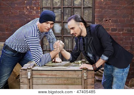 Two guys wrestle on wooden chest in depot
