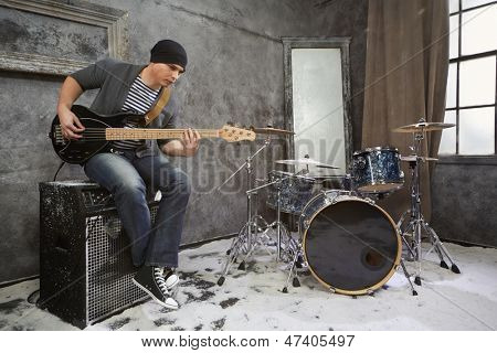 Young musician plays bass electric guitar sitting on amplifier in room powdered with snow