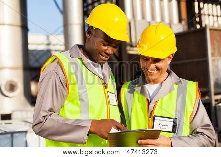 two heavy industry workers working in plant