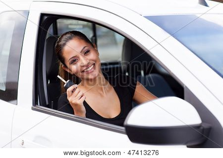 happy young woman showing a car key inside her just bought new vehicle