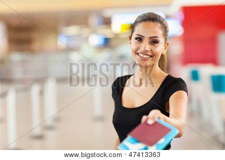 beautiful businesswoman handing over passport and air ticket at airport check in counter