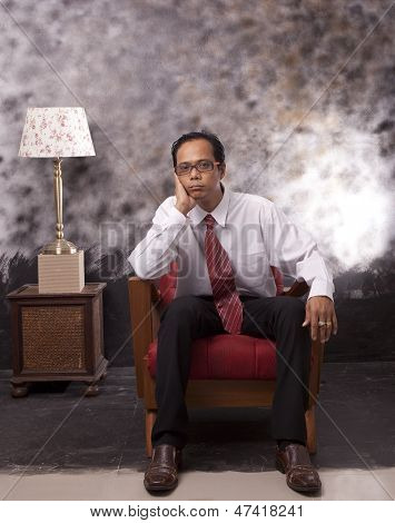 Business Man Sitting On Wood Sofa With Serious Face