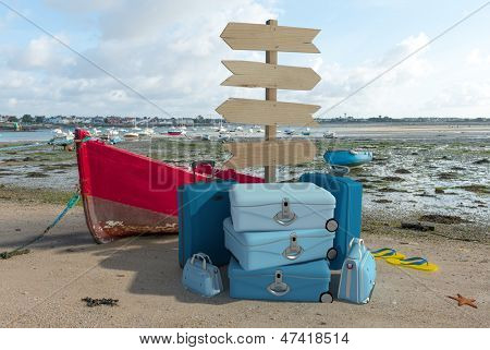 Pile of luggage and directional signs on a coastal landscape