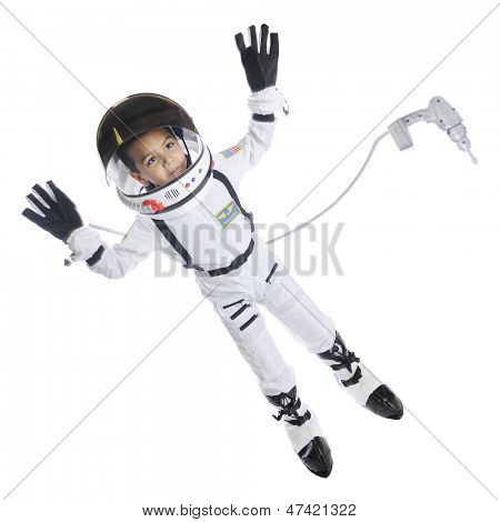 Full length image of an elementary astronaut in full gear floating in space.  He has an attached dress floating nearby.  On a white background.