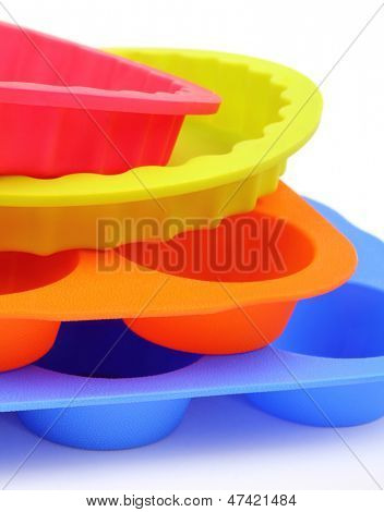A color silicone cake form and muffin molds on a white background
