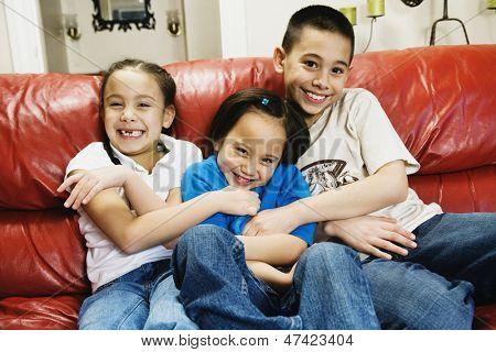 Asian siblings tickling sister